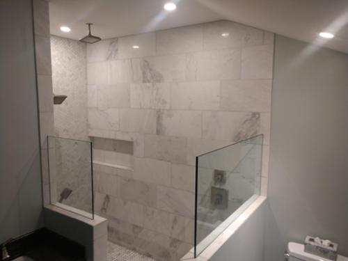 Over sized shower, Marble tile, 3 shower heads and custom glass.